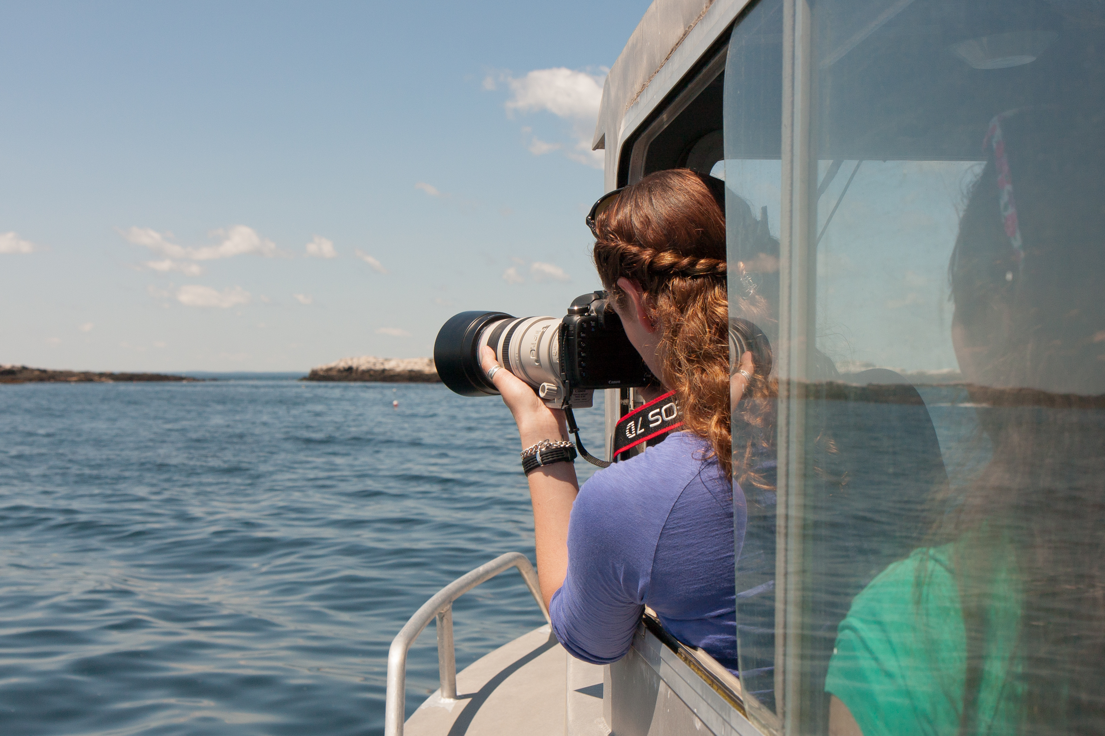Photo of marine mammal intern taking photos from SML research vessel